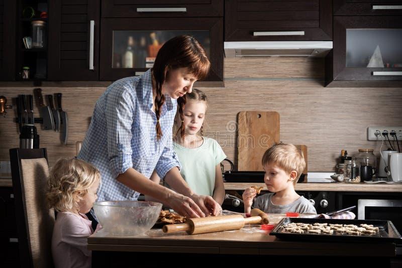 家庭时间:有准备曲奇饼的三个孩子的妈妈在厨房里 真正的地道家庭 免版税库存图片