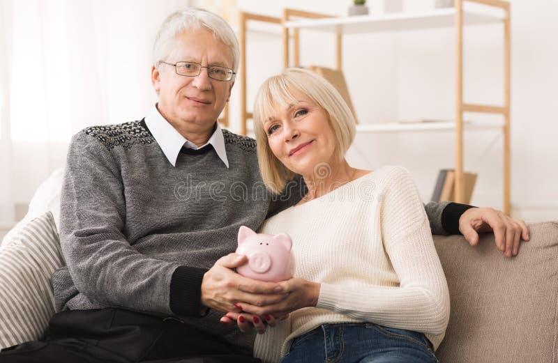 家庭预算 拿着piggybank和看照相机的资深夫妇 库存照片