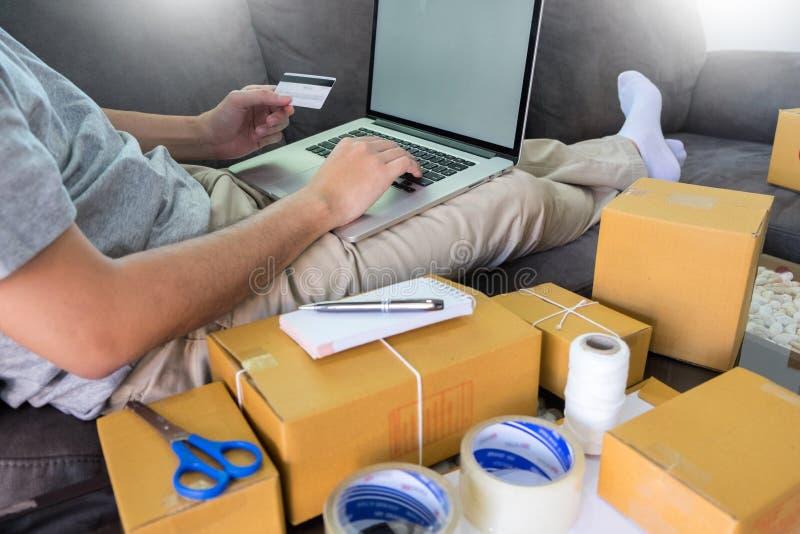 家和生活方式概念,买使用信用卡与包装起始的企业家小企业电子商务所有者一起使用 图库摄影