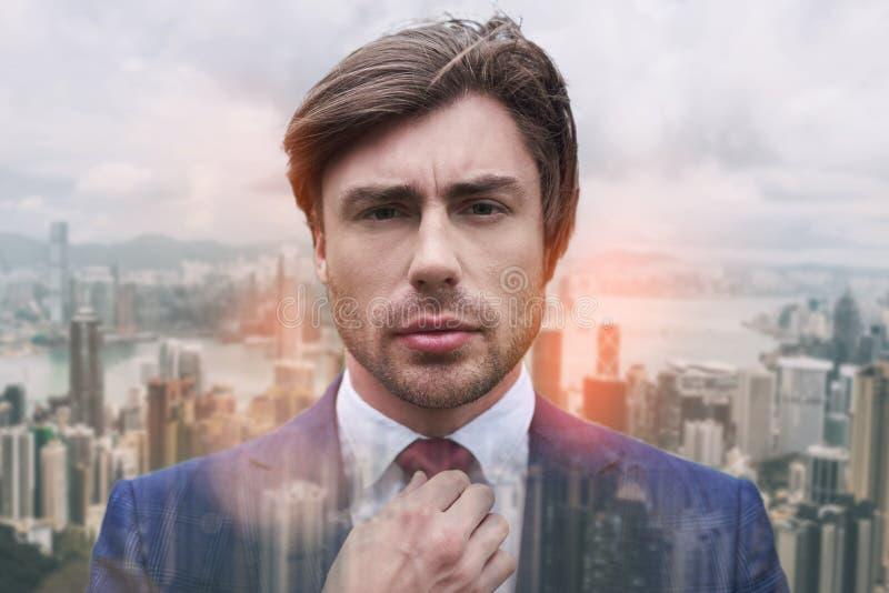 完全英俊 调整他的领带的英俊的年轻商人特写镜头画象,当站立反对时 免版税库存图片