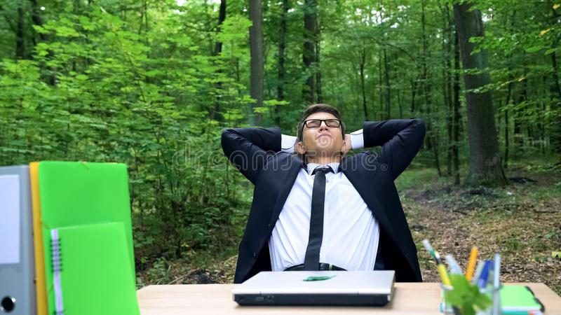 完成他的工作和放松在椅子的愉快的年轻商人在绿色森林里 库存照片