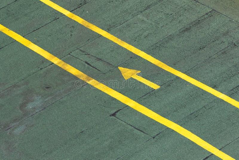 定向在一个绿色柏油碎石地面纹理地板上的交通黄色箭头 库存图片