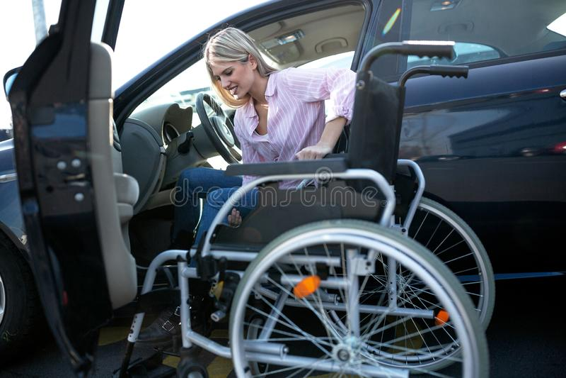 实际上移动的桃红色衬衣的挑战女孩从车向轮椅 库存照片
