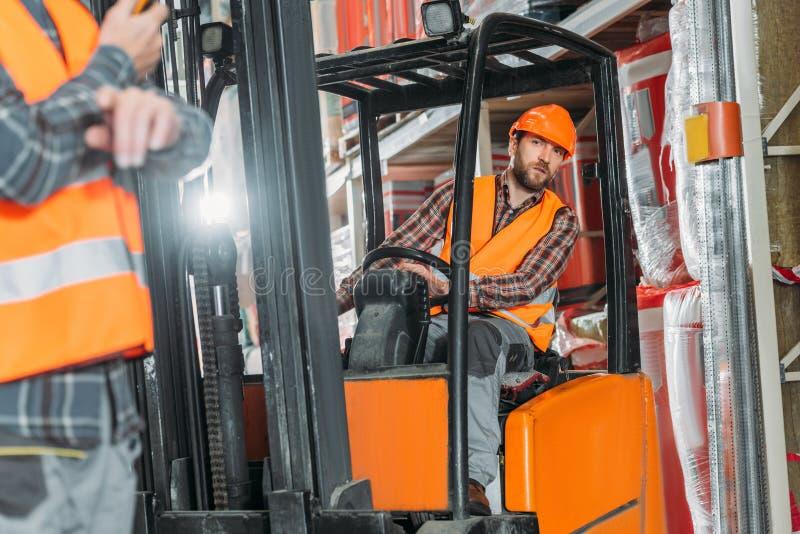 安全背心的坐在铲车机器的工作者和盔甲 免版税库存图片