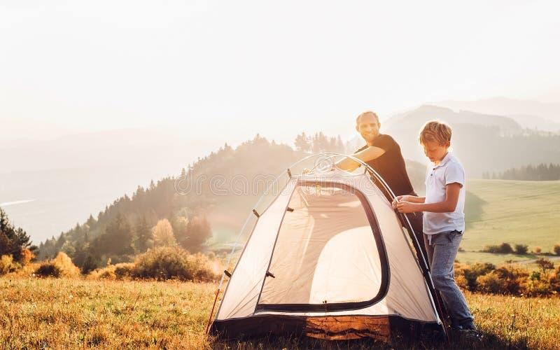 安装帐篷的父亲和儿子在森林沼地 迁徙与孩子概念图象 图库摄影
