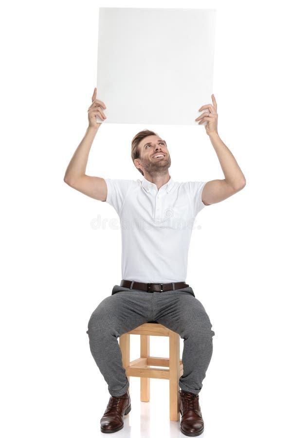 安装的愉快的偶然人拿着在他的头上的空白的委员会 免版税库存照片