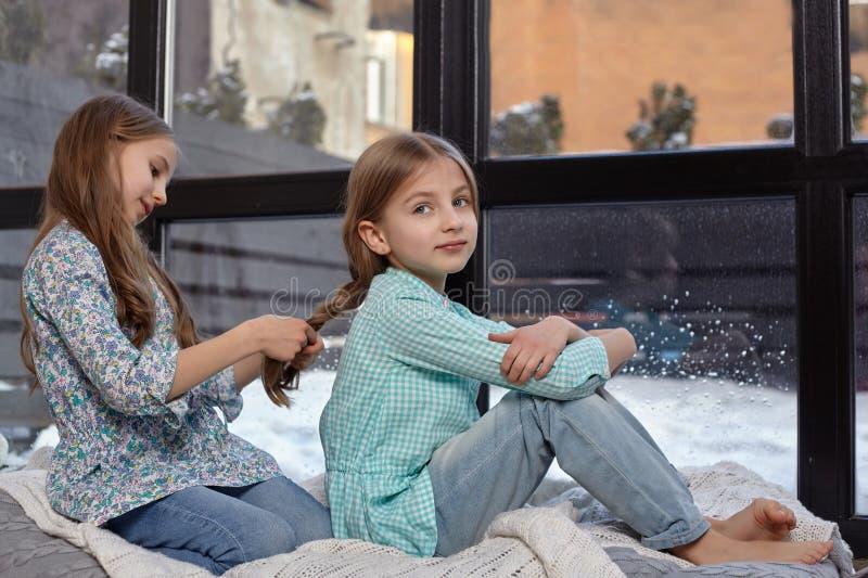 安静两个逗人喜爱的妹的图象坐在和平的窗台和 库存图片