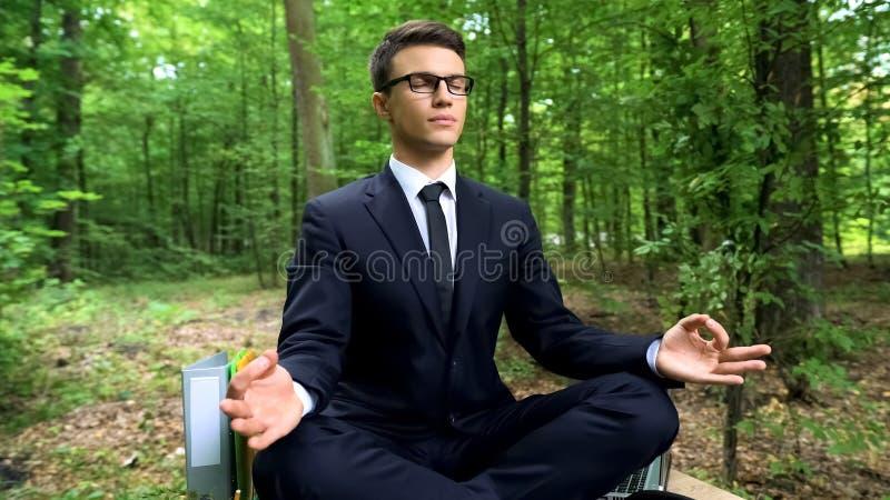 安静商人与闭上的腿盘的和眼睛坐书桌在森林里 免版税图库摄影