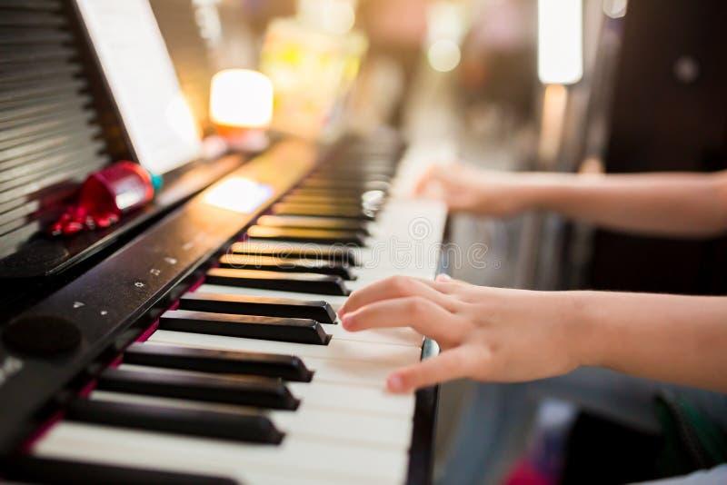 对弹在阶段的孩子的手的选择聚焦钢琴 免版税库存照片