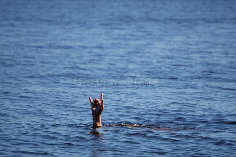 对在海水外面的男性手棍子在一个夏日,下沉一个人,拷贝空间的姿态 免版税库存图片