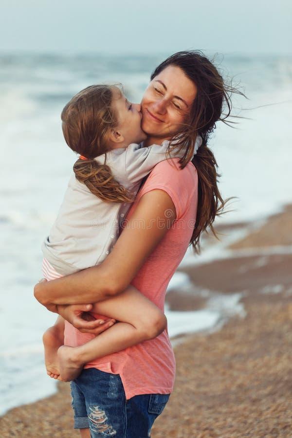 对母亲的爱在晚上时显示一个小女儿,当放松由海 免版税库存图片
