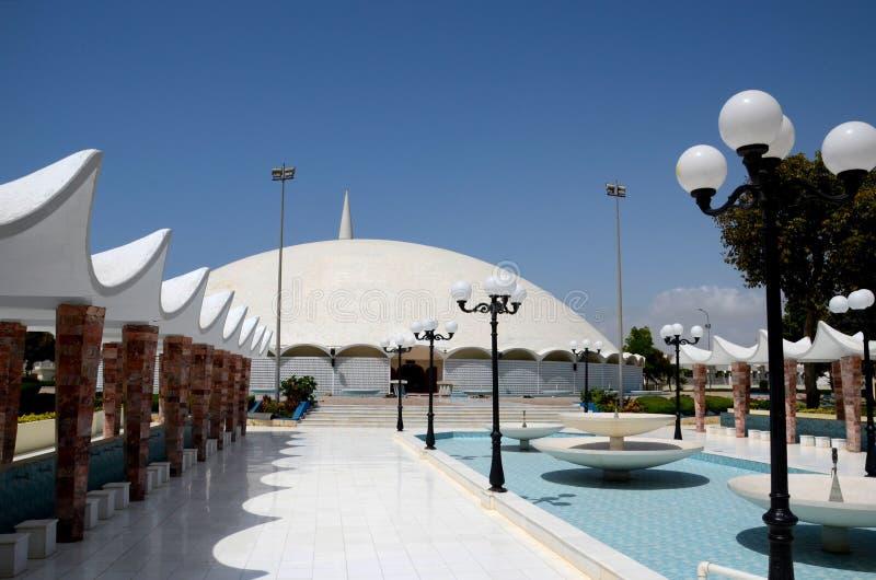 对Masjid Tooba或圆的清真寺的喷泉走道与大理石圆顶尖塔和庭院防御卡拉奇巴基斯坦 免版税库存照片