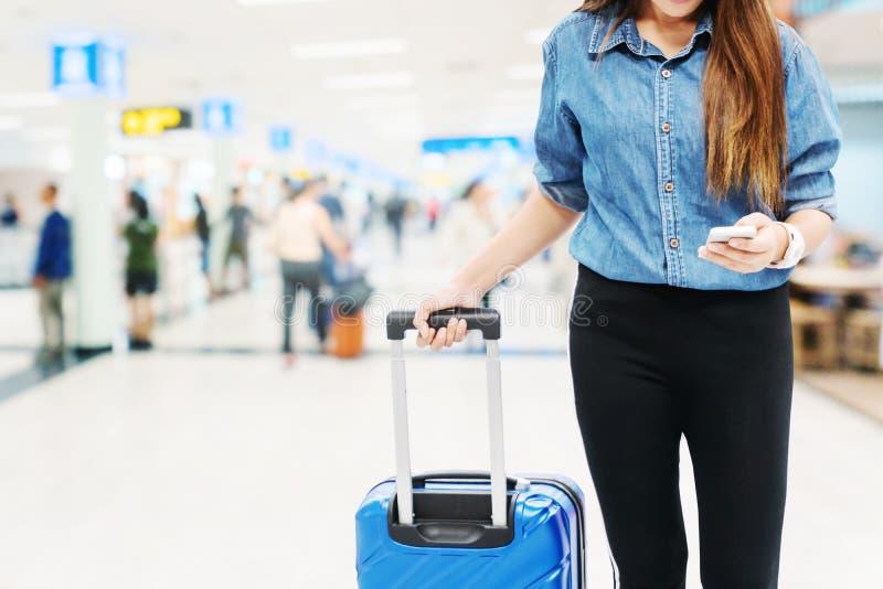 寻找在智能手机的亚裔旅客妇女飞行在机场终端旅行概念 库存图片