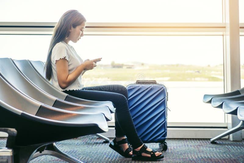寻找在智能手机的亚裔旅客妇女飞行在机场终端旅行概念 库存照片