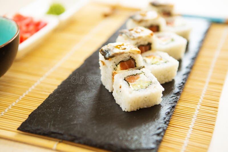 寿司集合nigiri和寿司卷在灰色石板岩在石背景 寿司菜单 日本食物 库存照片