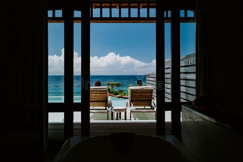 富有的夫妇在海滩胜地旅馆放松 库存照片