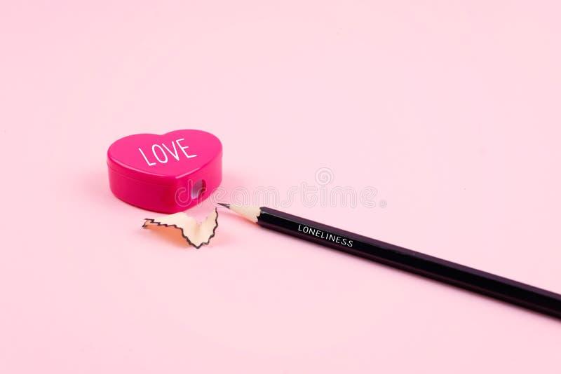 寂寞,爱,关系,言情概念 桃红色心脏铅笔刀和铅笔有削片的在桃红色背景 库存图片