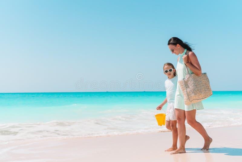 小可爱的女孩和年轻母亲热带海滩的 库存图片