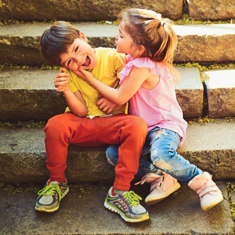 小女孩和男孩台阶的 关系 童年首先爱 小孩夫妇  男孩和女孩 使布赖顿椅子日甲板英国节假日懒人海边有风夏天的星期日靠岸 库存照片