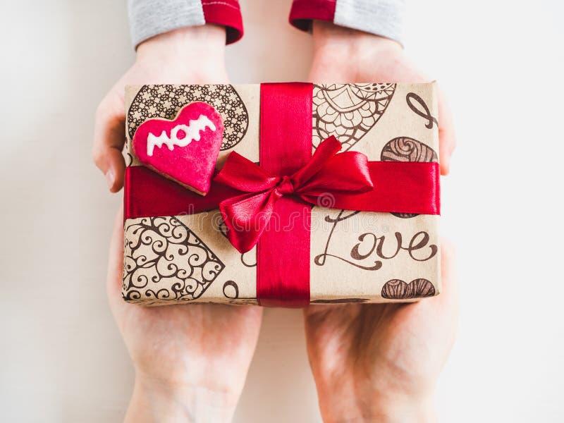 小孩子的手和一个箱子有礼物的 库存照片