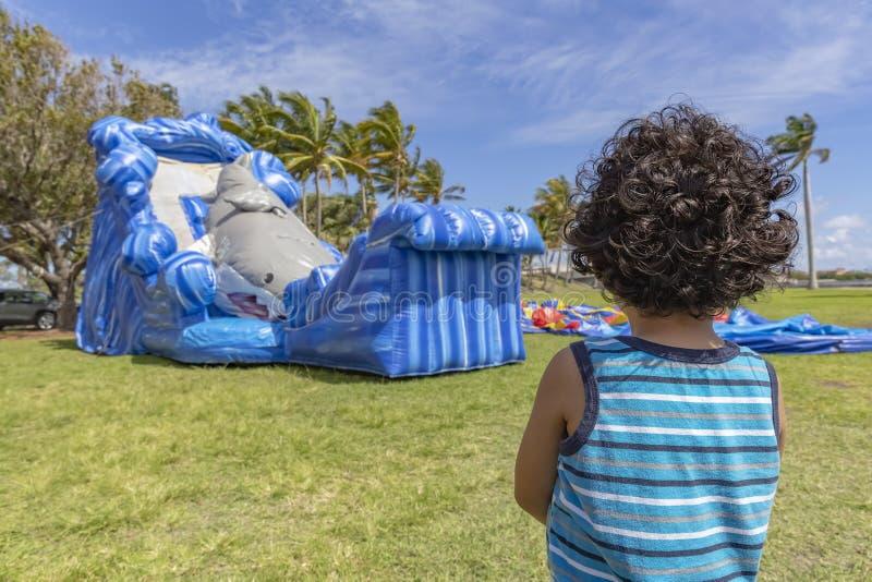 小孩站立非常仍然观看跳动房子膨胀 免版税图库摄影