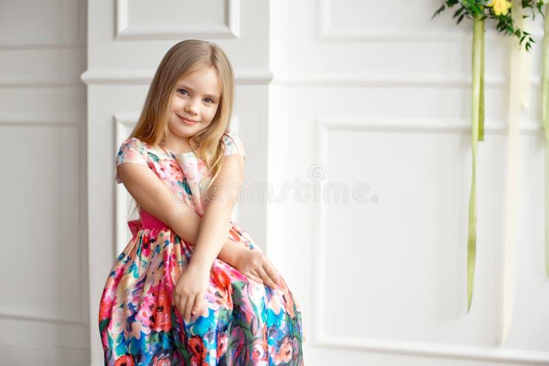 小微笑的女孩孩子画象五颜六色礼服摆在的室内 库存图片