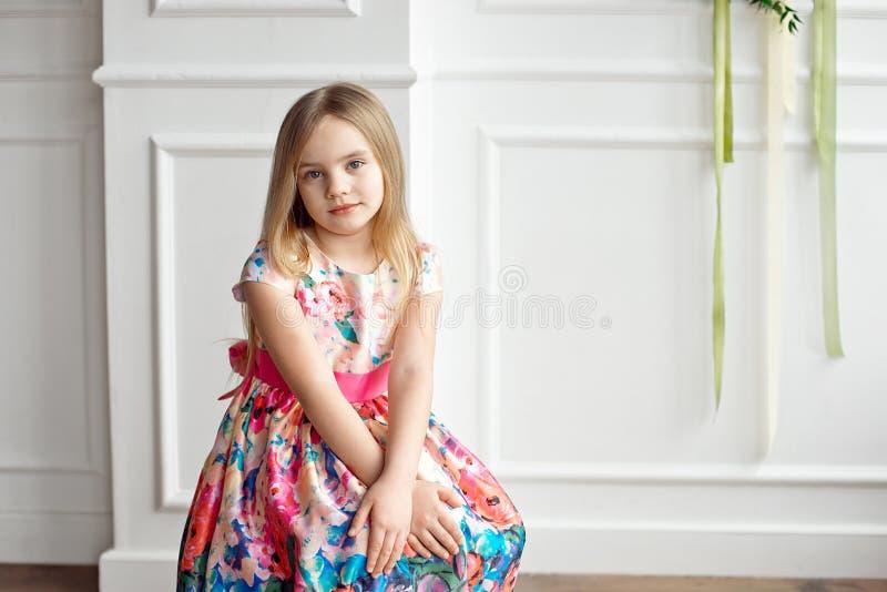 小微笑的女孩孩子画象五颜六色礼服摆在的室内 图库摄影