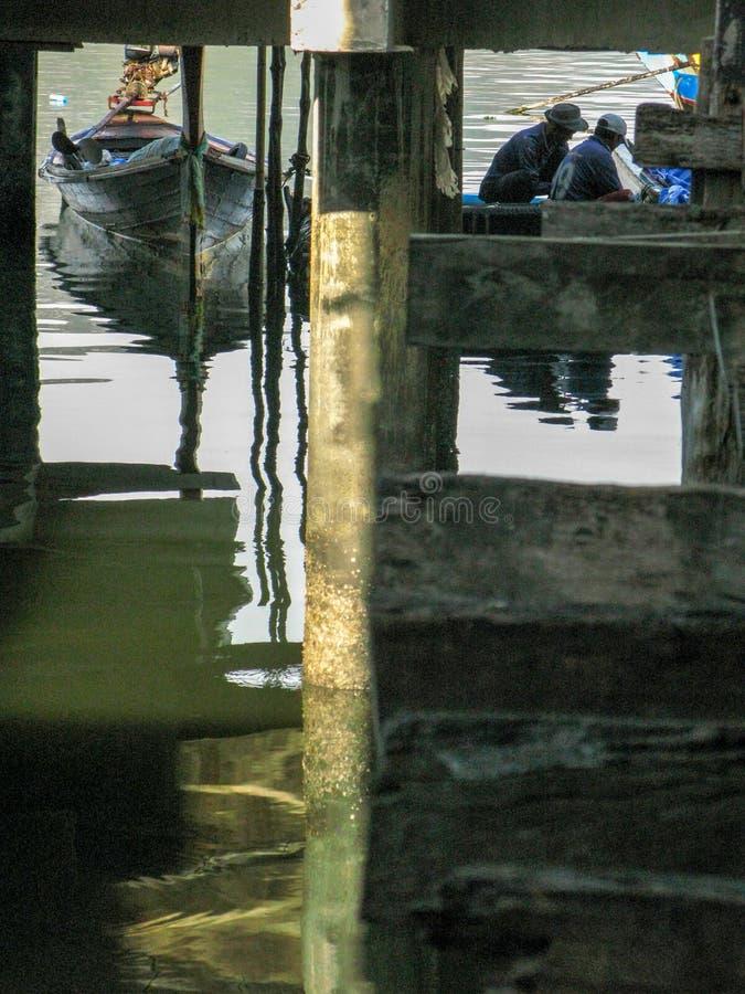 小渔船被停泊在海的桥梁下 免版税库存照片