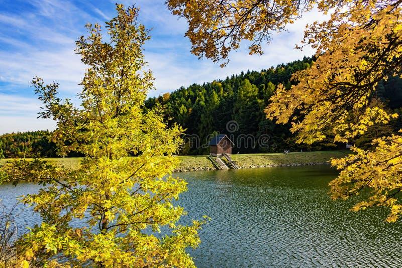 小木房子美丽的景色湖银行的在森林附近的在秋天期间 库存照片