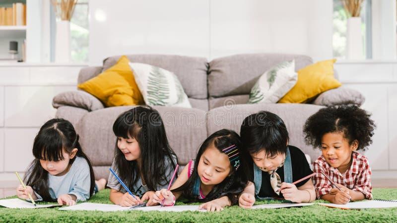 小组五个不同种族的年轻逗人喜爱的学龄前孩子,男孩和女孩愉快学习或者在家使一致或学校 免版税库存照片