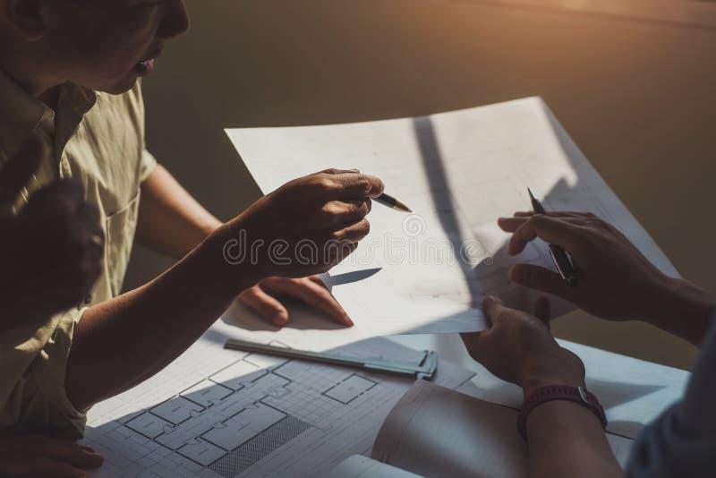 小组建筑师谈论与图纸在办公室设计计划 建筑和结构概念 库存照片