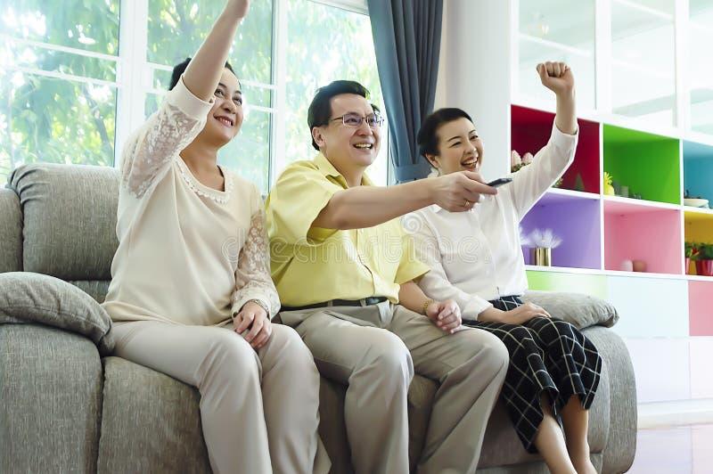 小组在家一起朋友看着电视坐舒适的沙发 图库摄影