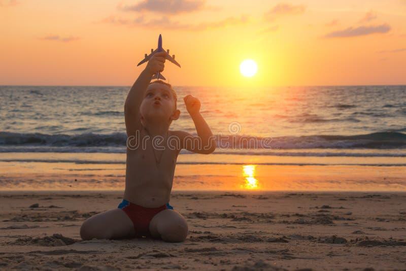 小男婴使用与在使热带海滩沙子的玩具飞机安达曼海惊奇在泰国在日落 库存图片