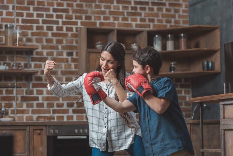 小男孩佩带的拳击手套和他的母亲实践的拳打 图库摄影