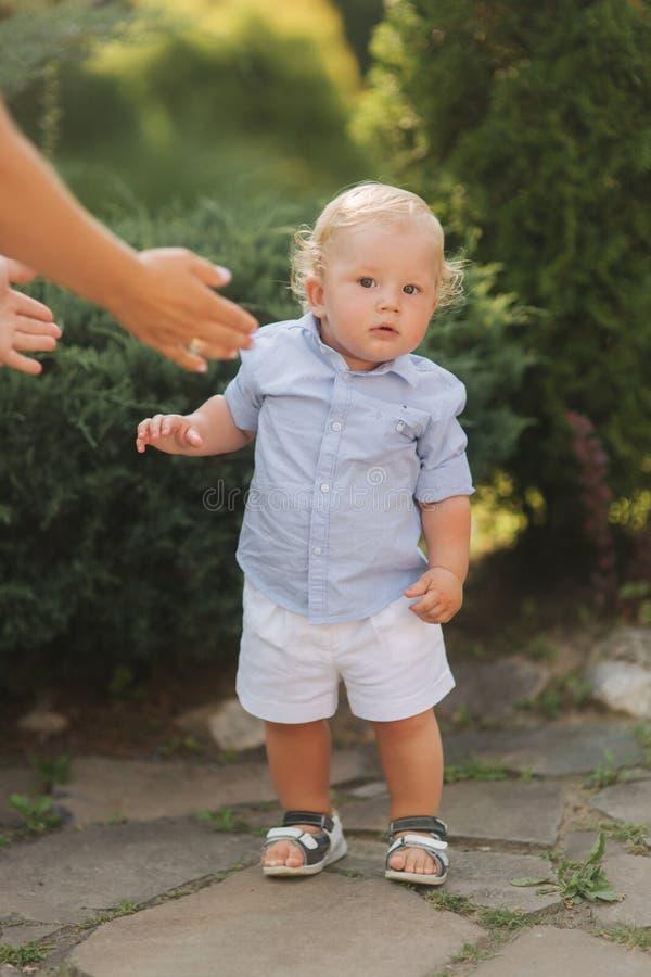 小男孩学会走 有金发外部的漂亮的孩子 免版税库存照片