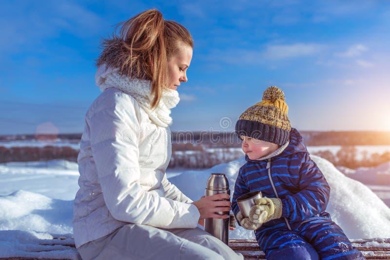 小男孩儿子2-3岁,坐长凳冬天在城市 妇女妈妈有一份热的汤饮料的藏品热水瓶 的treadled 免版税库存照片