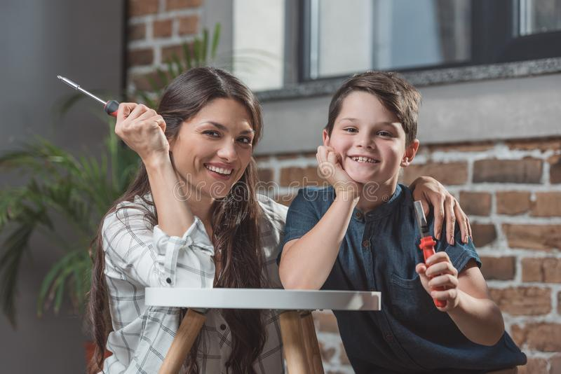 小男孩和他的年轻母亲在家坐倾斜在咖啡桌的地板 免版税库存图片