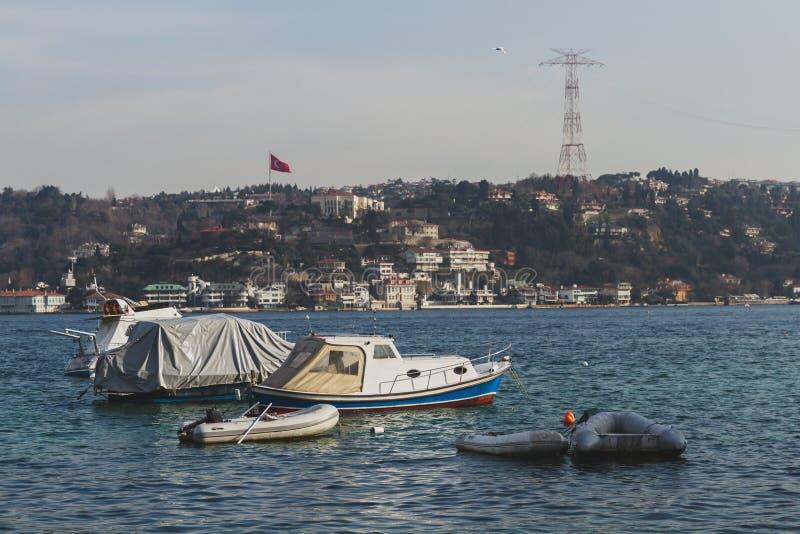 小船在博斯普鲁斯海峡海峡和房子小山的在伊斯坦布尔,土耳其 免版税库存图片