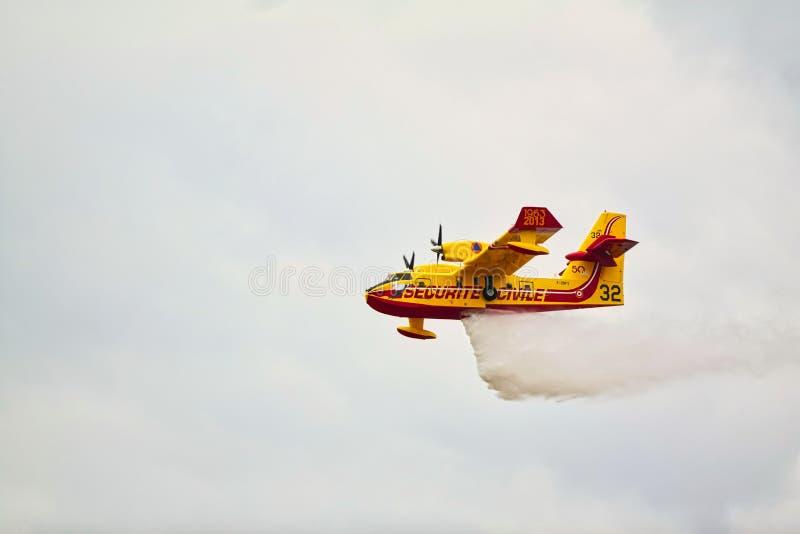小黄色红色水上飞机水上飞机飞行在天空droping的水中 免版税库存图片