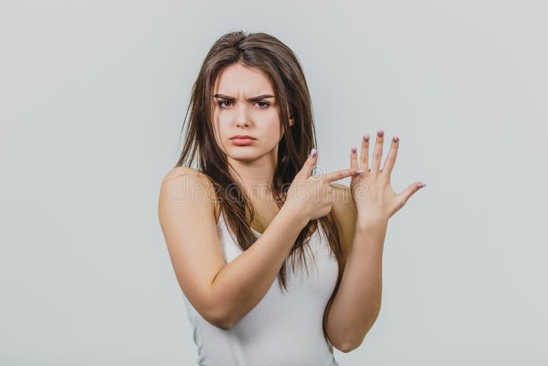 少女是相当白种人身分在白色背景中 显示食指到另一只手的手指 免版税库存图片