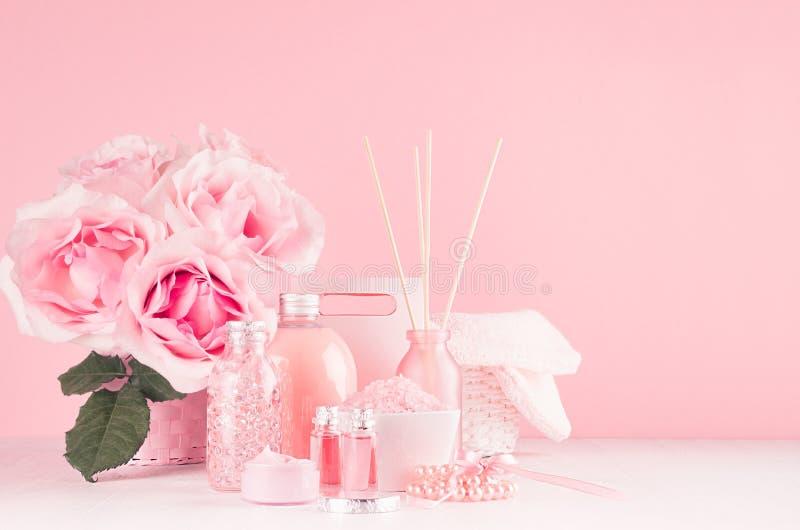少女逗人喜爱的卫生间内部与在淡色粉色的花-皮肤和身体关心的,在木头的芳香疗法化妆品 免版税库存照片