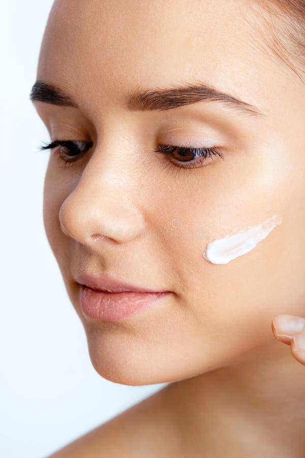 少妇喜欢面孔皮肤 应用在面孔的美丽的妇女画象奶油 拿着润湿的化妆水 r 库存照片
