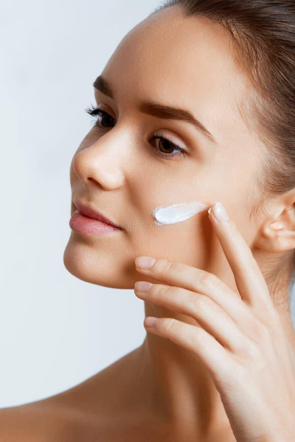 少妇的秀丽表面有装饰性的奶油的在面颊 护肤概念 免版税库存照片