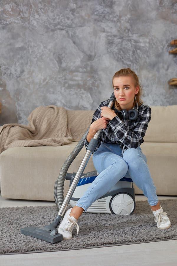 少妇用准备好清洁的设备清洗房子,在长沙发的开会 疲劳 库存图片