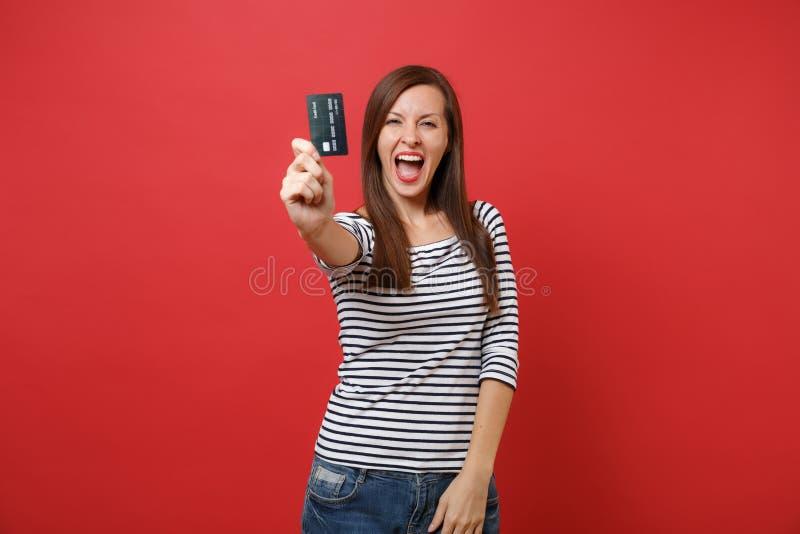 尖叫愉快的年轻女人画象偶然镶边衣裳的,显示在明亮的红色隔绝的照相机的信用卡 库存图片