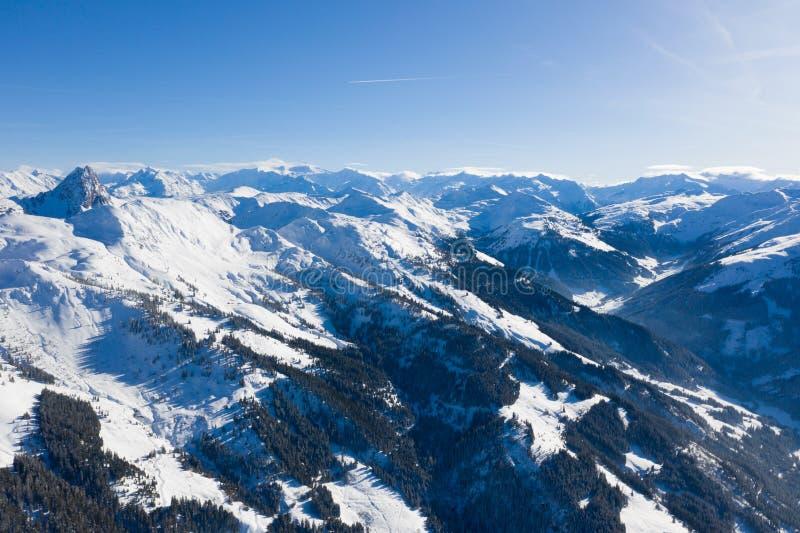 山脉明亮的全景与雪和冰的在反对天空蔚蓝的上面在冬天和密集的森林 免版税库存照片