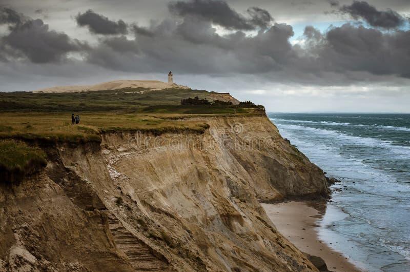 峭壁在Lonstrup,在一个沙丘的Rubjerg Knude灯塔在背景中,日德兰半岛北部,丹麦 库存照片