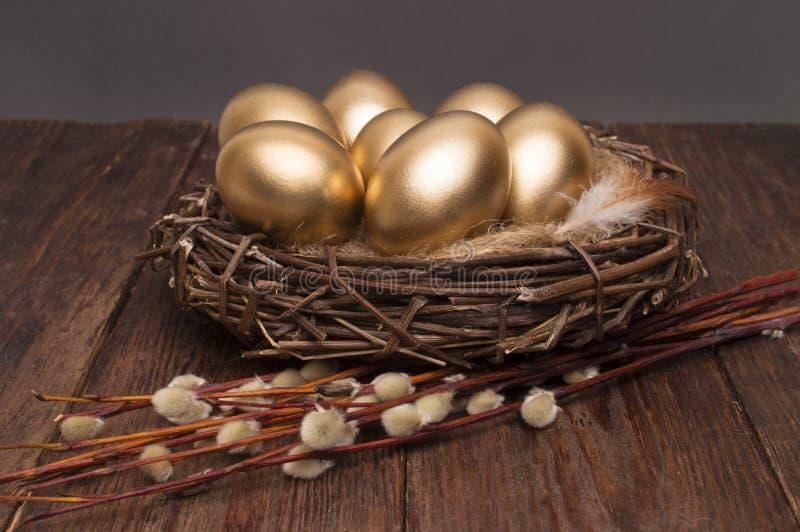 巢用与杨柳的金黄鸡蛋在木背景 复活节 免版税图库摄影