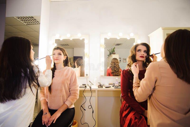 工作与美丽的年轻女人的专业化妆师 库存照片