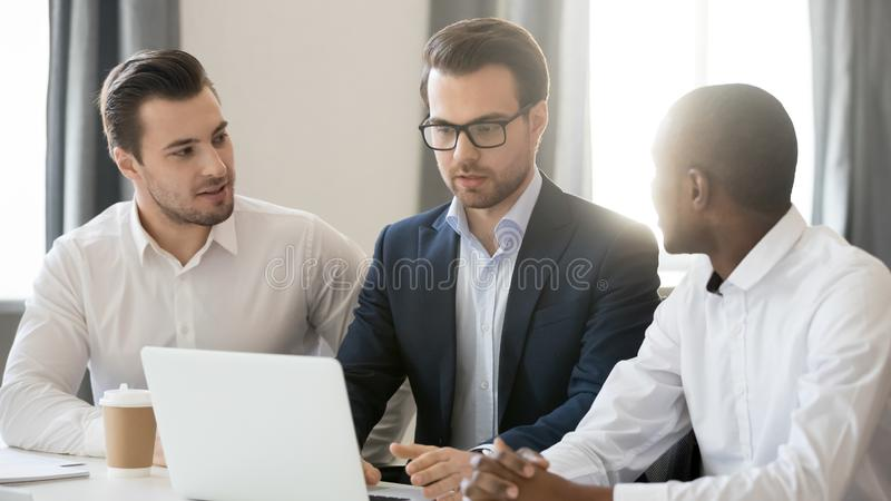 工作一起合作在膝上型计算机的三个不同的商人在办公室 库存图片
